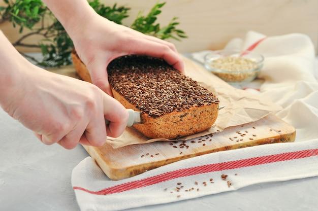 De handen van vrouwen sneed met een mes een stuk van eigengemaakt veganistbrood op een zuurdeeg van groen boekweit met lijnzaad, zonnebloem op een houten achtergrond.