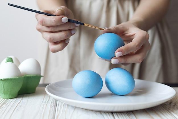 De handen van vrouwen versieren gekookte eieren voor pasen. hoge kwaliteit foto