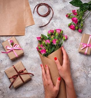 De handen van vrouwen wikkelen een boeket rozen in papier