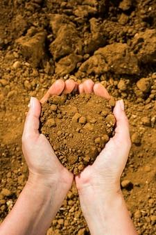 De handen van vuile heldere vuile vrouw houden droge losse grond