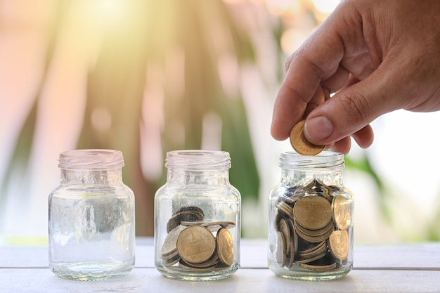 De handen van zakenman zetten een geld in glasfles en hebben gouden muntstuk.