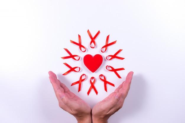 De handen worden zacht omarmd rood lint rond een rood hart op wit