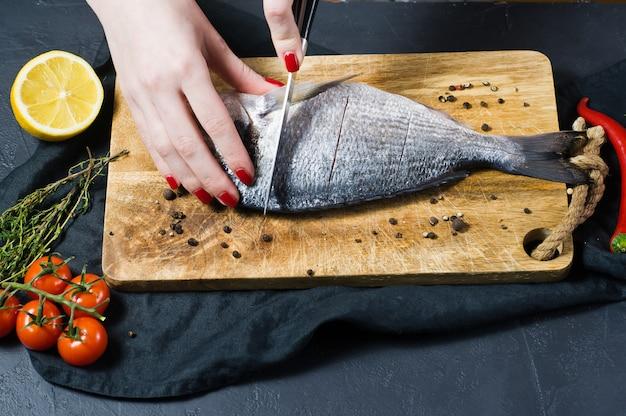 De handenchef-kok sneed dorado-vissen op een houten hakbord