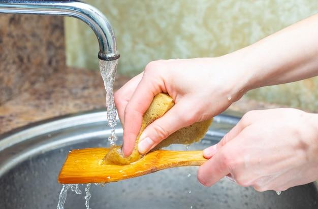 De handenclose-up van het meisje. het meisje wast de afwas onder stromend water. keuken kraan