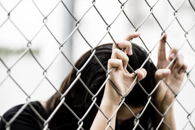 De handholding van de vrouw op de omheining van de kettingsverbinding voor vrijheid