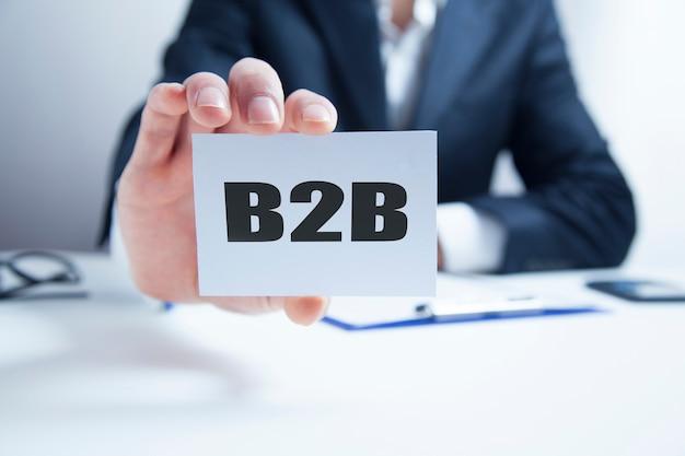 De handkaart van de zakenman met de inschrijving b2b