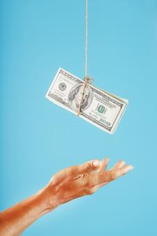 De handpalm strekt zich uit naar het geld dat aan een touw is opgehangen, op een blauwe achtergrond.
