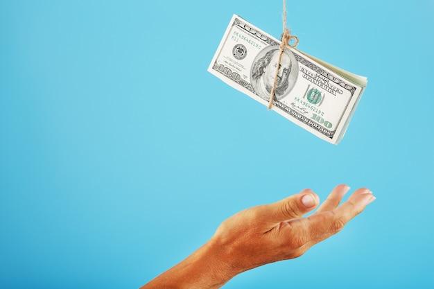 De handpalm strekt zich uit naar het opgeschorte geld