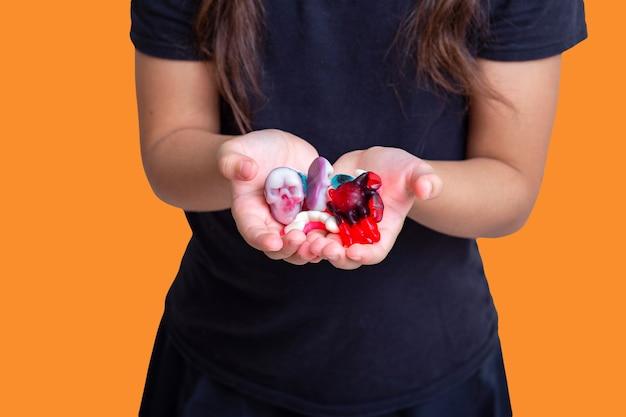 De handpalmen van een meisje in zwarte kleren op een halloweenfeest met een marmelade