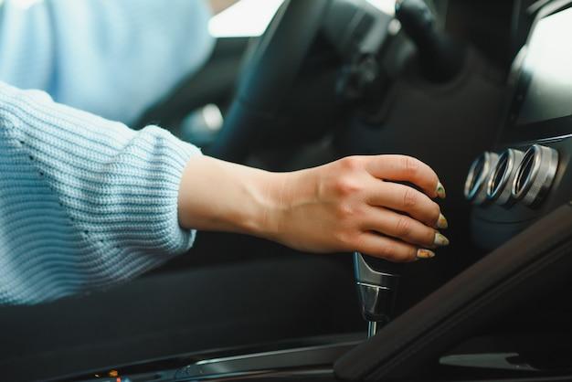 De handsnelheid van de vrouw schakelt tijdens het rijden in het voertuig