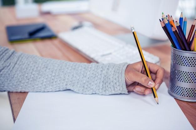De handtekening van de vrouw met potlood op wit blad in bureau