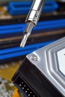 De harde schijf van een computer uit elkaar halen met een schroevendraaier om problemen op te sporen en te repareren.