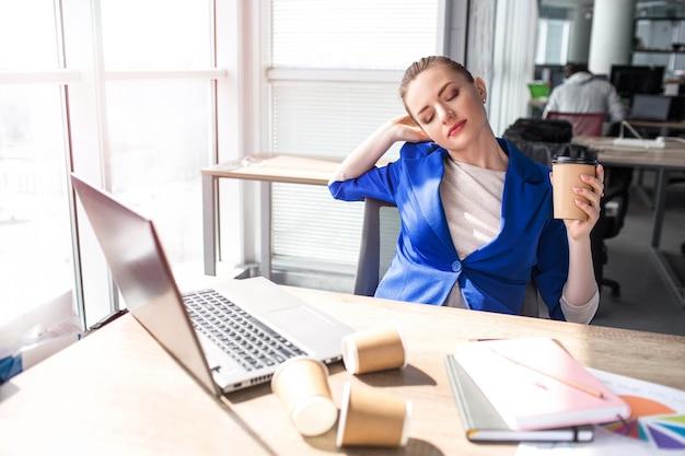 De hardwerkende vrouw zit aan tafel en rust uit