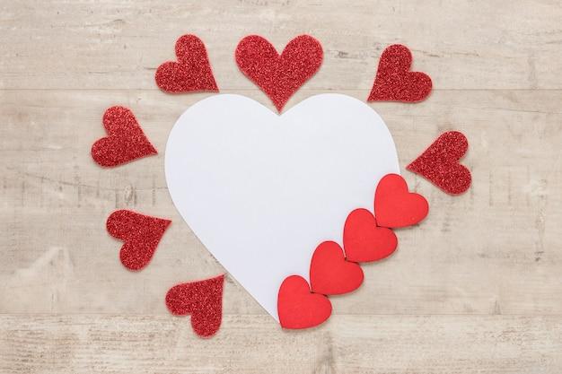 De harten van de valentijnskaartendag met document op houten achtergrond