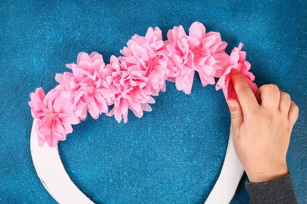 De hartvormige kroon verfraaide kunstbloem gemaakte roze papieren zakdoekjeservetten