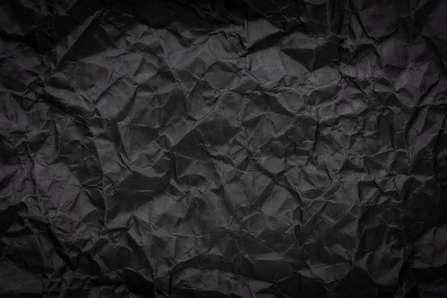 De haveloze verfrommelde donkere zwarte document textuurachtergrond