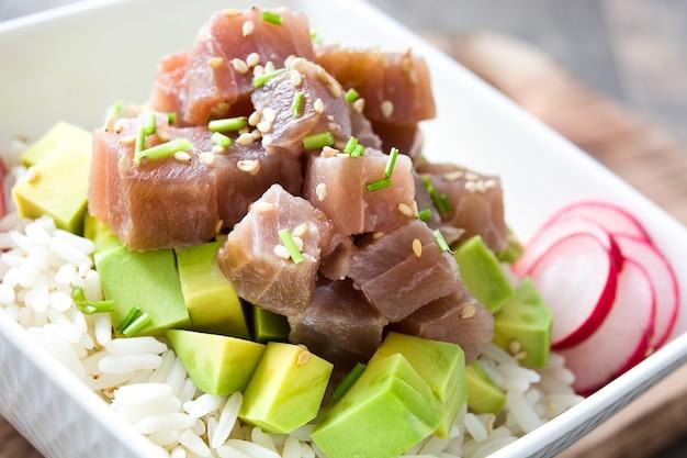 De hawaiiaanse kom van de tonijnpor met avocado, radijzen en sesamzaden op houten lijst sluit omhoog