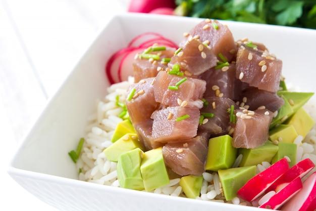 De hawaiiaanse tonijn porkom met avocado, radijzen en sesamzaden op witte houten lijst sluit omhoog