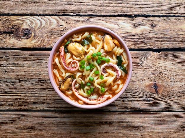 De heerlijke kruidige soep van de zeevruchtennoedel op de houten achtergrond. bovenaanzicht, kopie ruimte.