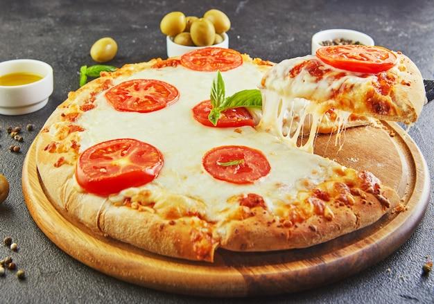 De heerlijke smaak van pizza en plakjes kaas met mozzarella en tomaten. driehoekspizza met uitrekkende kaas en kruiden