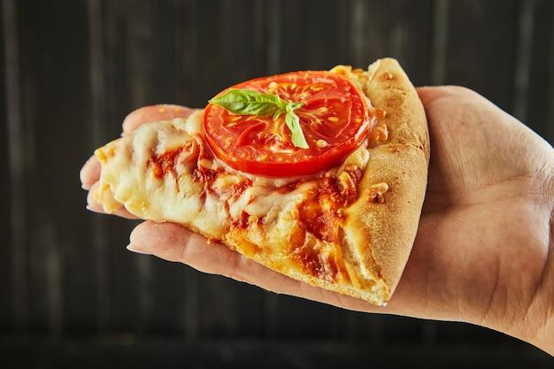 De heerlijke smaak van pizza en plakjes kaas met mozzarella en tomaten. hand met driehoek van pizza en kruiden