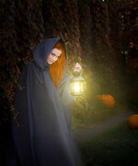 De heks staat 's nachts op straat en houdt een lantaarn vast