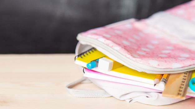 De heldere open schooltas met schoolbenodigdheden ligt op een bureau