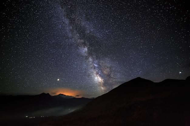 De heldere sterren van de melkweg aan de nachtelijke hemel boven de bergen van de noord-kaukasus.