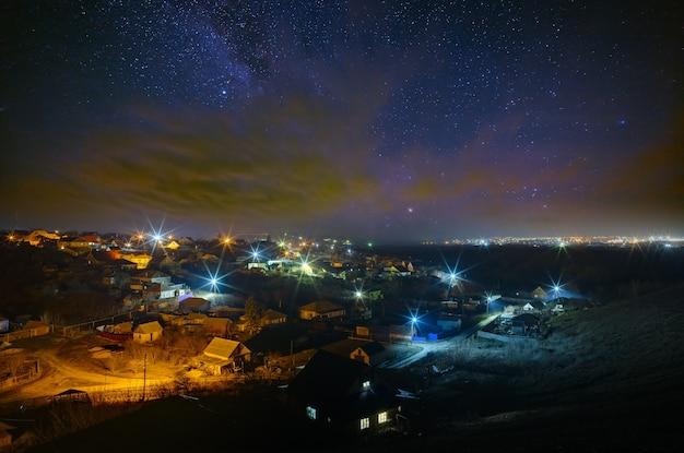 De heldere sterren van de melkweg met wolken aan de nachtelijke hemel boven de stad