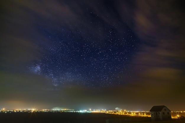 De heldere sterren van de melkweg met wolken in de nachtelijke hemel boven de stad. lichtvervuiling door straatlantaarns.