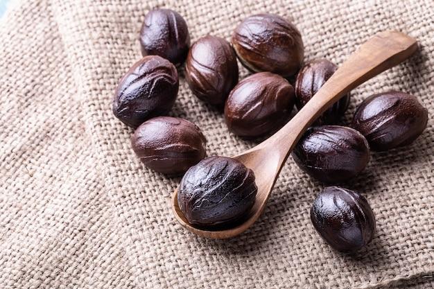 De hele notemuskaat verspreidt noten op de jute