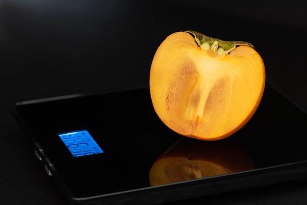 De helft van de persimmon is op een elektronisch gewicht op een zwarte achtergrond.