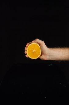 De helft van een sappige sinaasappel in de hand van de man op zwarte achtergrond