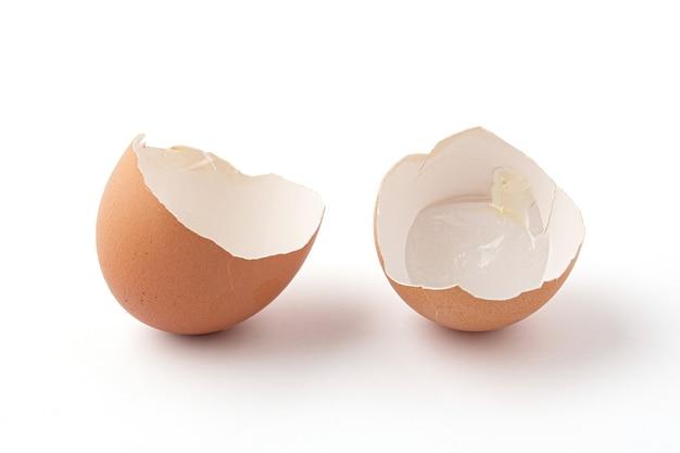 De helft van gebroken eierschalen geïsoleerd op een witte achtergrond. de eierschaal is in 2 stukken gebroken. eierschalen zijn ovaal, bruin, broos en dun, gemakkelijk te breken.