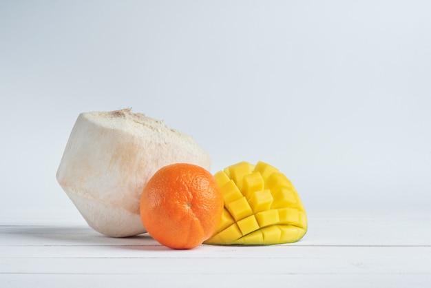 De helft van mango, mandarijn en verse kokosnoot