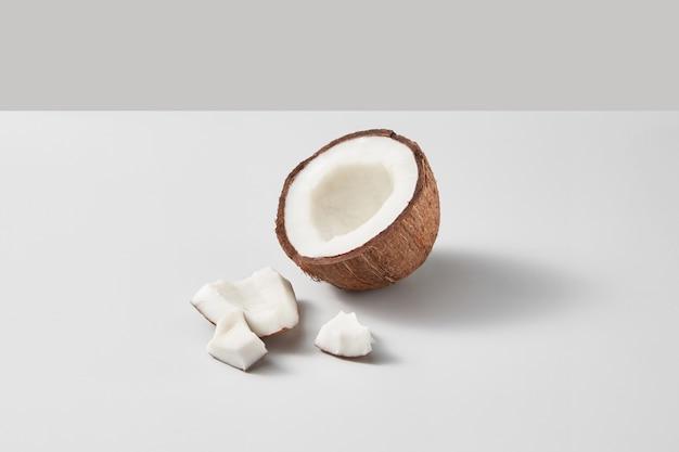 De helft van vers rijp organisch tropisch kokosfruit op een lichtgrijze duotoonachtergrond met zachte schaduwen en exemplaarruimte. veganistisch concept.