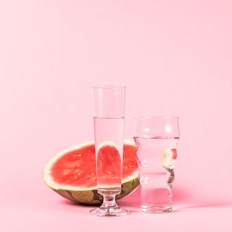 De helft watermeloen en glazen met water