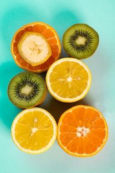 De helften van sinaasappelenbananen kiwi en citroenen op een blauwe lijst