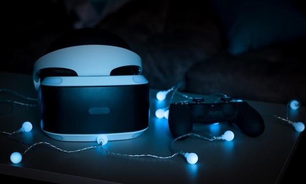 De helm van virtual reality. nieuwe ervaring in het spel. verbazingwekkende emoties, koele rust. virtual reality-brillen liggen in neonlichten.
