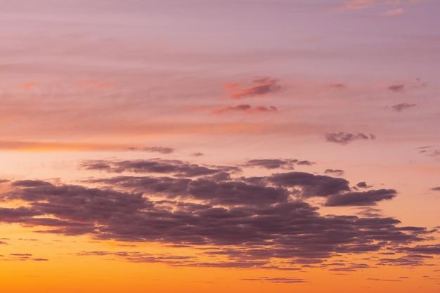 De hemel bij zonsondergang met heldere vlekken van oranje en roze