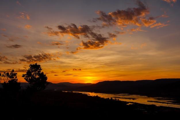 De hemel van de silhouetzonsopgang over rivier en berg