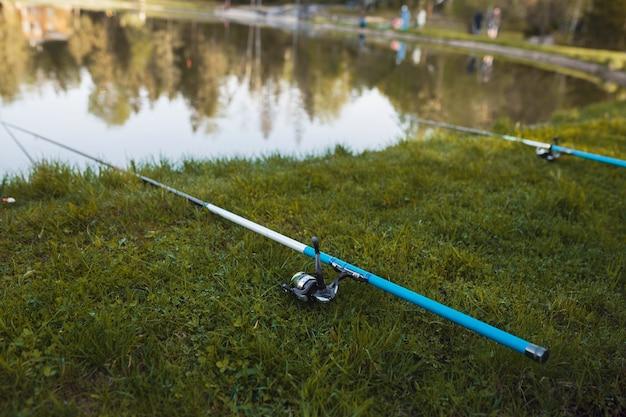 De hengel ligt op het groene gras bij het meer