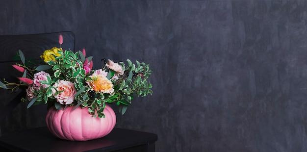 De herfst bloemenboeket in gekleurde pompoenvaas op zwarte stoel, ba