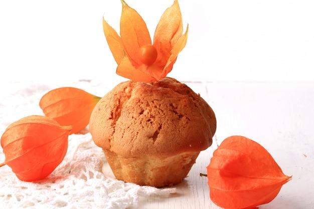 De herfst verse eigengemaakte cupcakes met de witte kruisbes van de kantkaap op hout