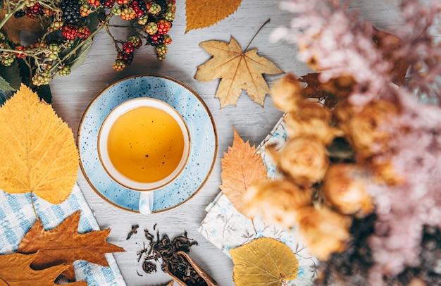 De herfst verwarmende thee op een houten lijst met bladeren die van de de herfstboom dichtbij liggen