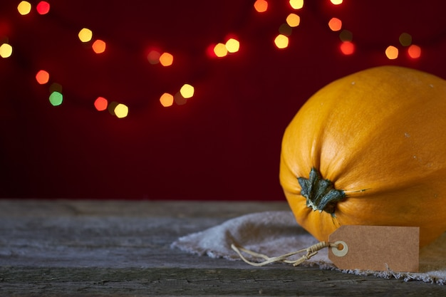 De herfstachtergrond op een donkere houten oppervlakte, gele pompoen op een achtergrond van onscherpe lichten, selectieve nadruk