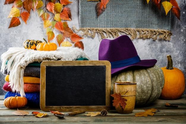De herfstachtergrond op houten tabel tegen de oude uitstekende muur van de roestvoorwaarde