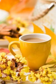 De herfstbanner met kop van koffie met kaneel op wit hout