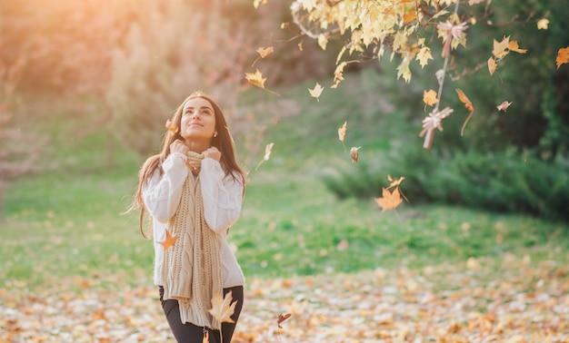 De herfstbladeren die op gelukkige jonge vrouw in bos vallen. portret van heel mooi meisje in herfst park
