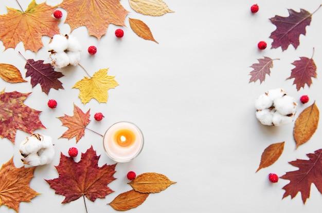 De herfstbladeren en kaars op witte achtergrond